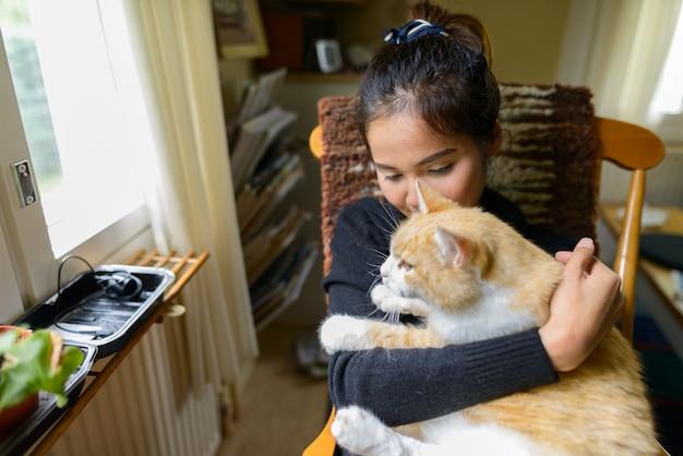 Retrato de uma jovem linda mulher asiática sentada e relaxando com o gato de estimação em casa
