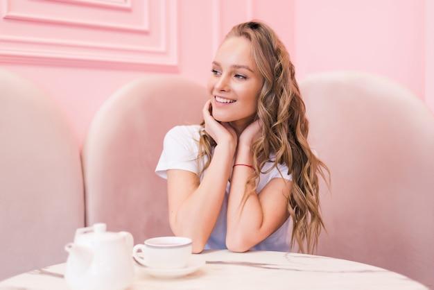 Retrato de uma jovem linda mulher bebendo chá em um café moderno durante o intervalo do trabalho