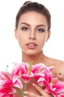 Retrato de uma jovem linda mulher caucasiana com lírios cor de rosa isolados