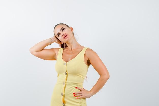 Retrato de uma jovem linda mulher cobrindo a orelha com a mão, mantendo a mão no quadril no vestido e olhando pensativa para a frente