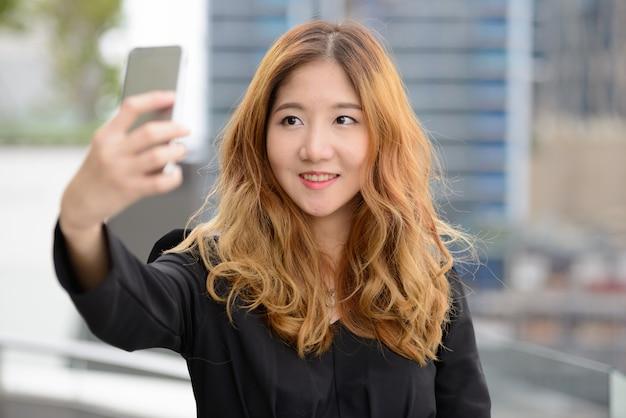 Retrato de uma jovem linda mulher de negócios asiática contra a vista da cidade ao ar livre