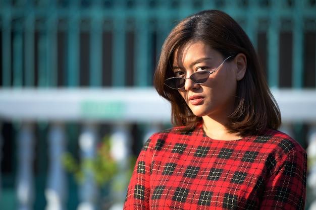 Retrato de uma jovem linda mulher de negócios asiática usando óculos escuros na rua ao ar livre