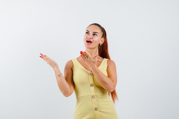 Retrato de uma jovem linda mulher espalhando as palmas das mãos no vestido e olhando surpresa para a frente