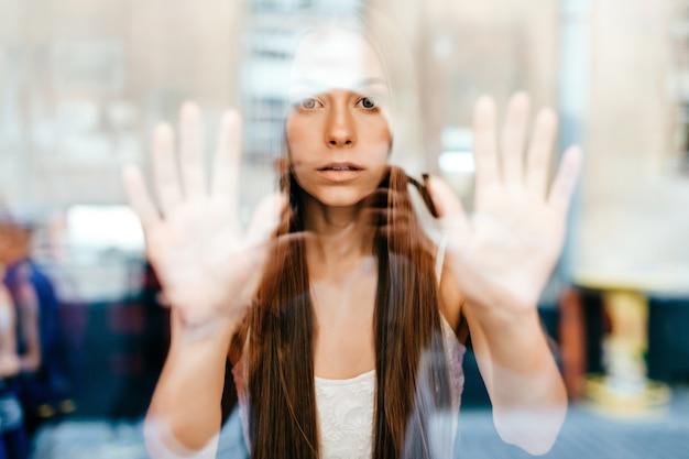 Retrato de uma jovem linda romântica menina morena com cabelo comprido, posando atrás de um vidro.