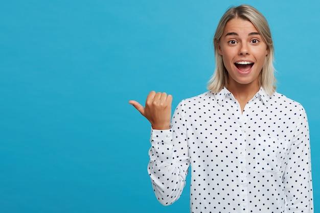 Retrato de uma jovem loira adorável, confiante e feliz, usando uma camisa de bolinhas, sorrindo e mostrando os polegares isolados sobre a parede azul