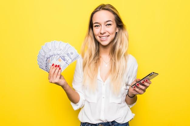 Retrato de uma jovem loira animada mostrando um monte de notas de dinheiro e segurando o celular isolado sobre a parede amarela