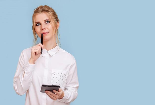 Retrato de uma jovem loira atraente com olhos azuis, trabalhando em um tablet. uma jovem designer freelancer empreendedora ponderou o projeto