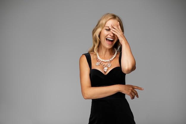 Retrato de uma jovem loira atraente em um vestido preto coquetel usando joias caras e grânulos de pérolas rindo tocando sua testa com a mão.
