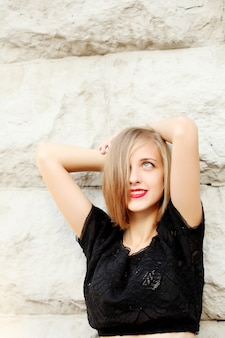Retrato de uma jovem loira com batom vermelho nos lábios em uma camiseta preta curta