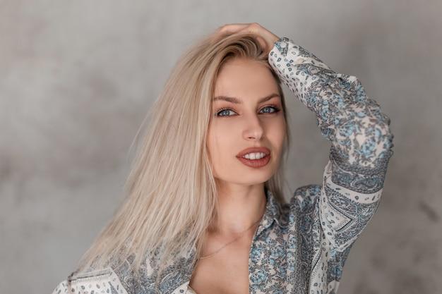 Retrato de uma jovem loira com olhos azuis e lábios carnudos e sensuais em uma camisa cinza da moda com um padrão em um estúdio perto da parede