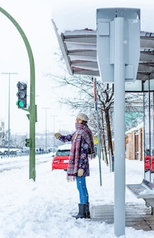Retrato de uma jovem loira com roupas de inverno, esperando na parada do ônibus. neve na cidade.