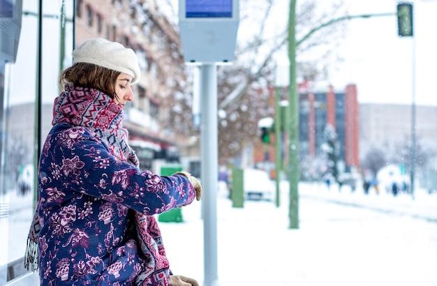 Retrato de uma jovem loira com roupas de inverno, sentado na parada do ônibus. neve na cidade.