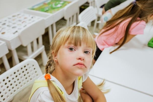 Retrato de uma jovem loira com síndrome de down com cauda, sentado na mesa branca com outras crianças e estudando.