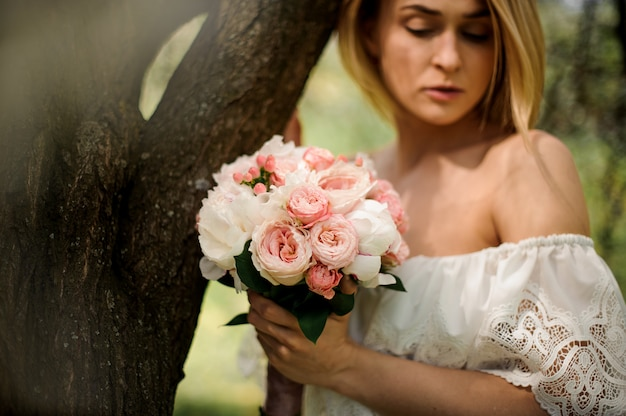 Retrato de uma jovem loira com um buquê de flores em pé perto da árvore