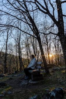 Retrato de uma jovem loira com um rabo de cavalo sentado em uma paisagem natural na extremadura, espanha, ao pôr do sol.