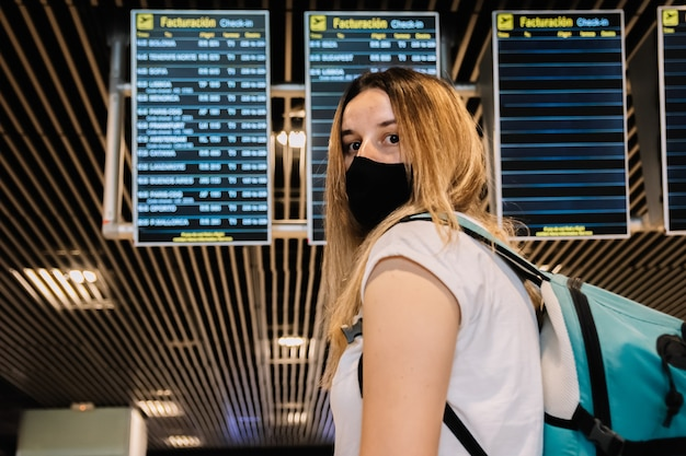 Retrato de uma jovem loira com uma máscara facial, olhando para as telas de informações de voos do aeroporto.