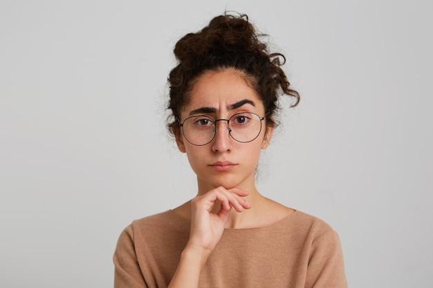 Retrato de uma jovem loira concentrada séria usando uma camisa de bolinhas com as mãos postas, parecendo pensativo e pensando isolado sobre a parede branca