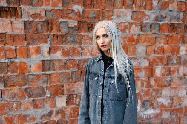 Retrato de uma jovem loira contra uma parede de tijolo vermelho