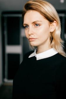 Retrato de uma jovem loira de cabelos curtos elegante em roupas pretas formais, posando dentro de casa