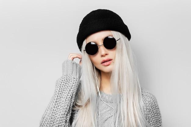 Retrato de uma jovem loira de óculos escuros redondos e chapéu preto do beanie.