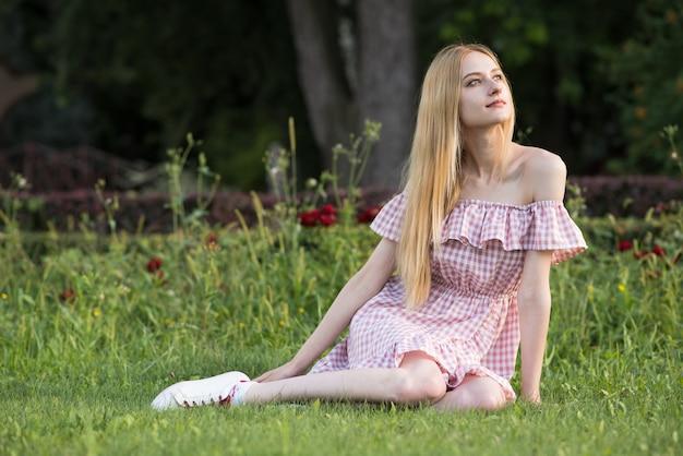 Retrato de uma jovem loira e atraente caucasiana. a garota está sentada na grama no pasto. senhora feliz posando.