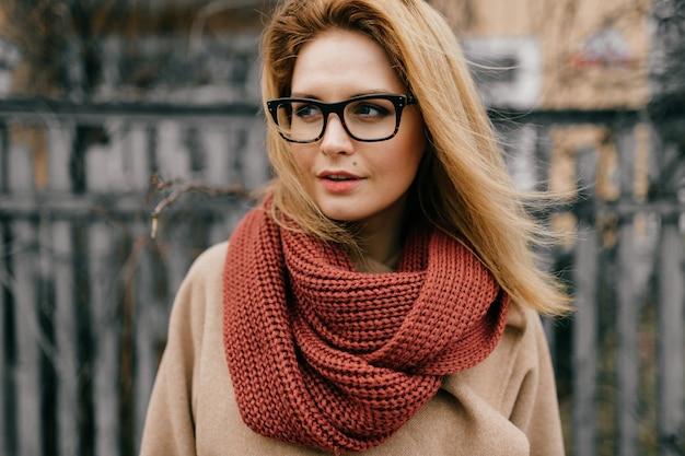 Retrato de uma jovem loira elegante com óculos e lenço posando ao ar livre