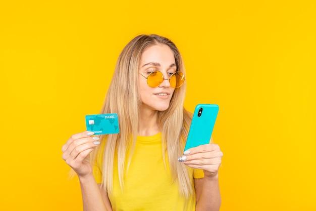 Retrato de uma jovem loira em óculos de sol, mostrando o cartão de crédito de plástico ao usar o telefone celular.