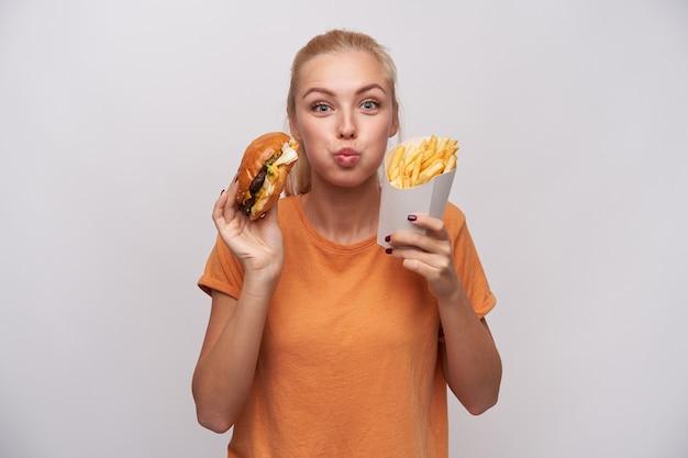 Retrato de uma jovem loira encantadora segurando junk food e olhando alegremente para a câmera, estufando as bochechas e animada com um jantar saboroso, isolado sobre fundo branco