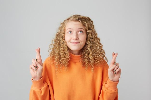 Retrato de uma jovem loira encaracolada com os dedos cruzados e os olhos olhando para cima enquanto faz um desejo antigo