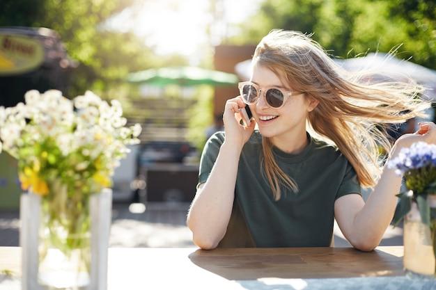 Retrato de uma jovem loira falando em seu telefone celular rosa com amigos ou amantes da mídia social usando óculos