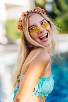 Retrato de uma jovem loira feliz de cabelos longos, biquíni azul e coroa de flores na cabeça
