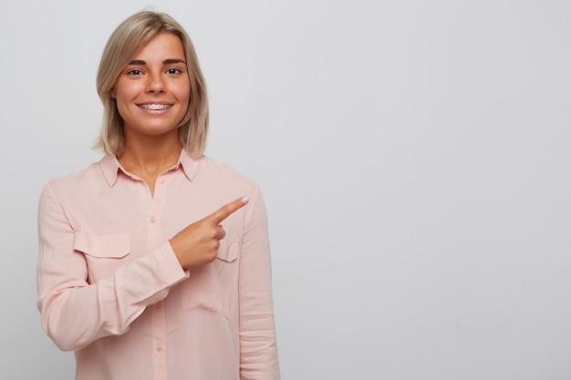 Retrato de uma jovem loira linda e alegre com aparelho nos dentes e usa uma camisa rosa parece confiante e aponta para o lado com o dedo isolado sobre a parede branca