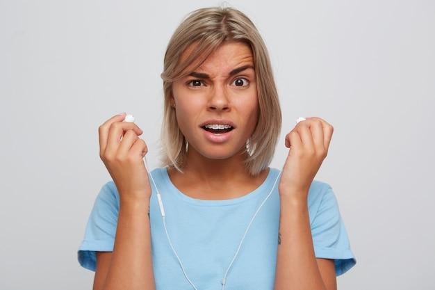 Retrato de uma jovem loira linda e confusa com aparelho nos dentes e usa uma camiseta azul parece envergonhado e segurando fones de ouvido isolados sobre a parede branca