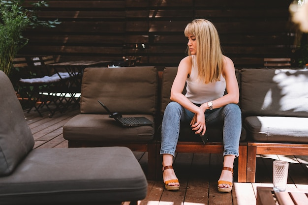 Retrato de uma jovem loira linda sentada com um laptop e um telefone no sofá em uma área de trabalho aconchegante