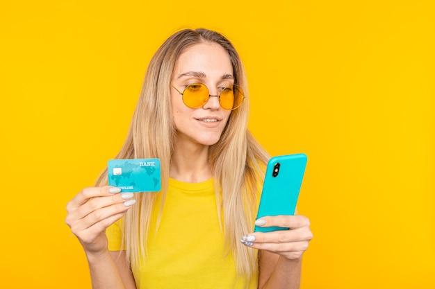 Retrato de uma jovem loira mostrando um cartão de crédito de plástico ao usar um telefone celular isolado sobre o amarelo