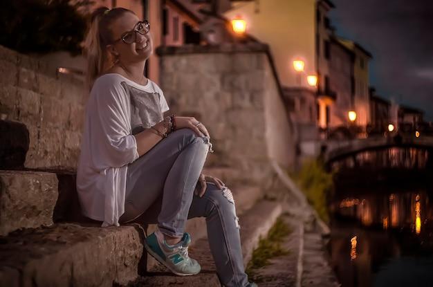 Retrato de uma jovem loira sentada na escadaria perto de um riacho à noite