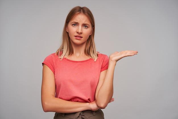 Retrato de uma jovem loira séria com penteado casual vestindo uma camiseta rosa em pé sobre um fundo branco, levantando a palma da mão de maneira confusa e franzindo as sobrancelhas enquanto olha para a câmera