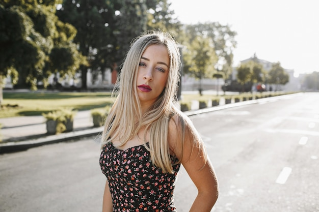 Retrato de uma jovem loira sexy com maquiagem diária está de pé no meio da estrada