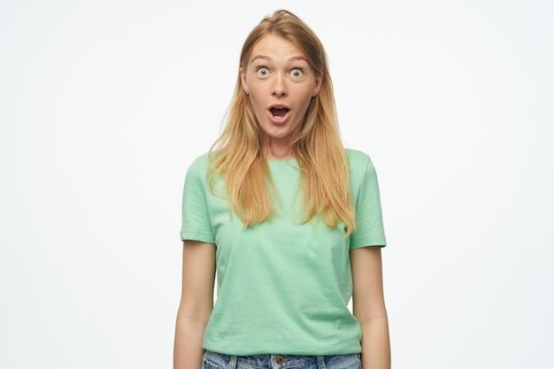 Retrato de uma jovem loira surpresa, vestindo uma camiseta verde, olhando para a câmera com os olhos bem abertos e expressão facial chocada
