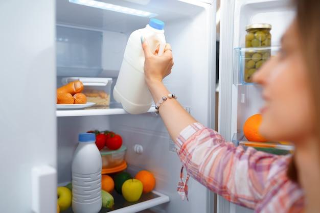Retrato de uma jovem loira tirando comida de sua geladeira