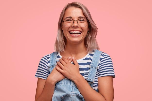 Retrato de uma jovem loira vestindo macacão jeans