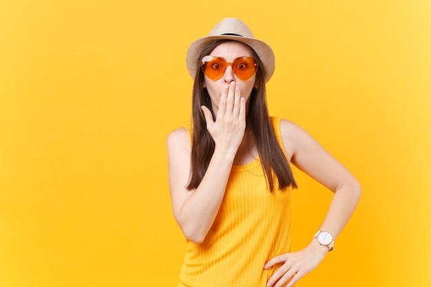 Retrato de uma jovem louca diversão chocada com chapéu de palha de verão, óculos laranja cobrem a boca de mão, copie o espaço isolado em fundo amarelo. emoções sinceras de pessoas, conceito de estilo de vida. área de publicidade.