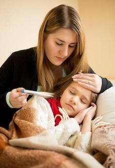 Retrato de uma jovem mãe abraçando a filha doente e verificando o termômetro