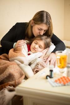 Retrato de uma jovem mãe carinhosa beijando a filha doente na cama
