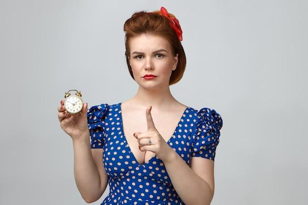 Retrato de uma jovem mãe carrancuda e irritada usando batom vermelho, penteado retrô e vestido elegante com decote decote segurando um despertador vintage, avisando sua filha adolescente para voltar para casa a tempo