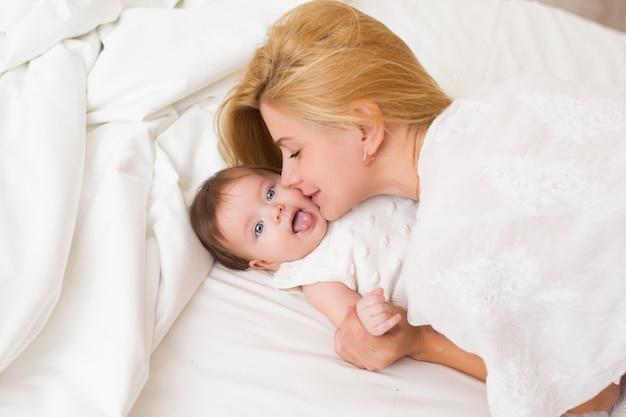 Retrato de uma jovem mãe com cabelo loiro com sua doce menina de 3 meses de idade vestida de branco, se divertindo no quarto pela manhã, amando o conceito de família feliz, vista de cima