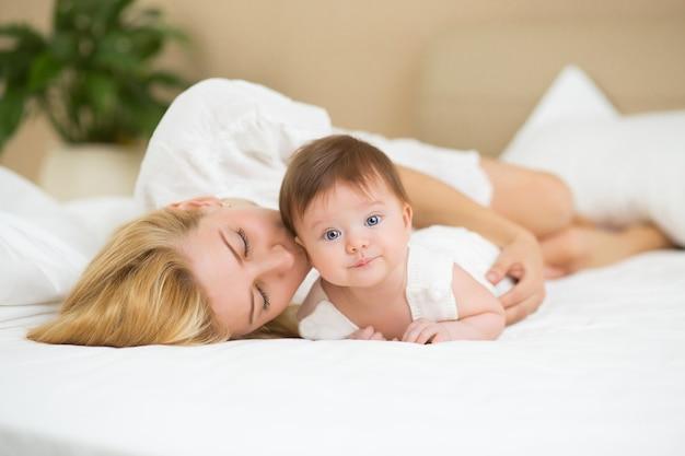 Retrato de uma jovem mãe com cabelo loiro com sua doce menina de 3 meses de idade vestida de branco, se divertindo no quarto pela manhã, amando o conceito de família feliz