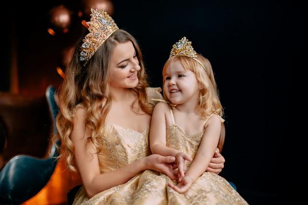 Retrato de uma jovem mãe e filha em vestidos luxuosos