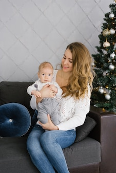 Retrato de uma jovem mãe em um suéter branco e seu jovem filho. eles estão sentados no sofá perto da árvore de natal