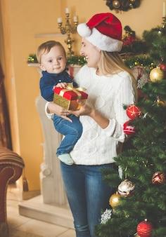 Retrato de uma jovem mãe feliz abraçando seu filho no boné do papai noel na árvore de natal